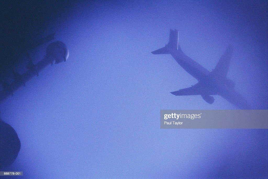 Airplane in flight, low angle view (blue tone) : Stock Photo
