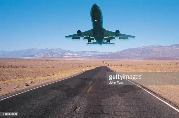 Airplane in flight on empty highway