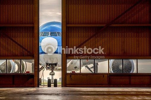 airplane in front of half opened door to hangar ストックフォト