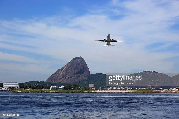 Airplane landing at the airport Aeroporto Santos Dumont Rio de Janeiro Brazil In the background the Sugarloaf Mountain Pao de Acucar
