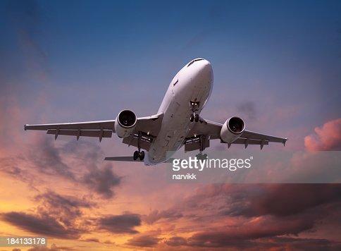 Airplane landing in sunset light