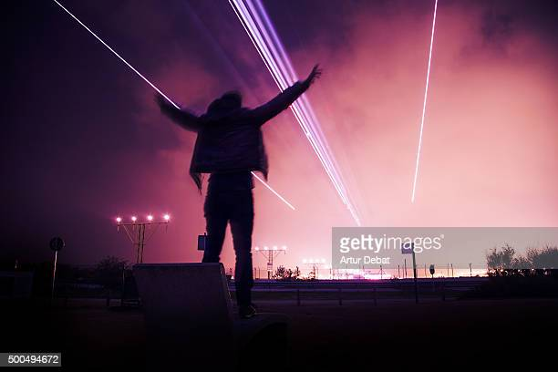Airplane landing in the Barcelona El Prat airport at night with excited man with arms raised.