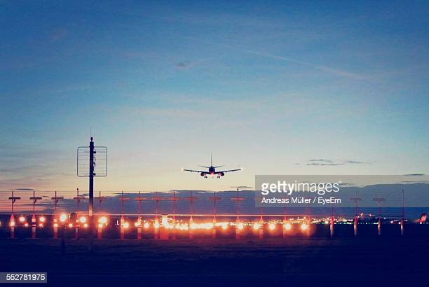 Airplane Landing On Runway At Dusk