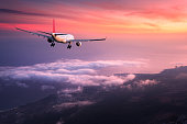 Airplane. Landscape with big white passenger airplane is flying in the red sky over the clouds at colorful sunset. Journey. Passenger airliner is landing at dusk. Business trip. Commercial plane