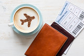 Airplane made of cinnamon in cappuccino, passports  and boarding passes on white background