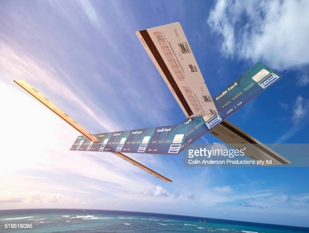 Airplane made out of credit cards flying over ocean