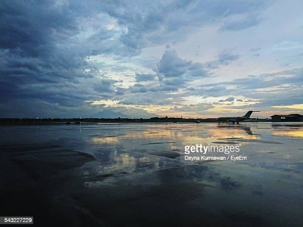 Airplane On Airport Runway Against Cloudy Sky During Sunset