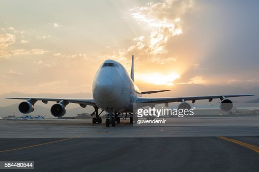 Airplane on taxiway at sunset