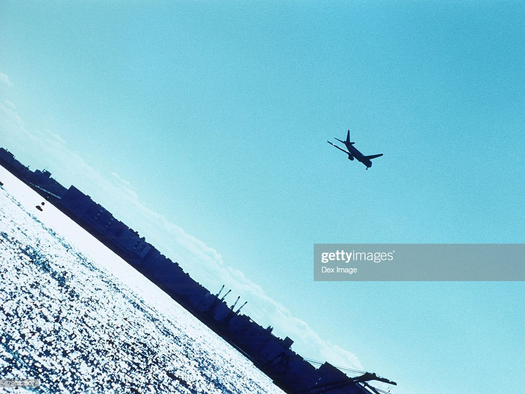 Airplane over harbor, silhouette, Tokyo Bay, Japan : Stock Photo