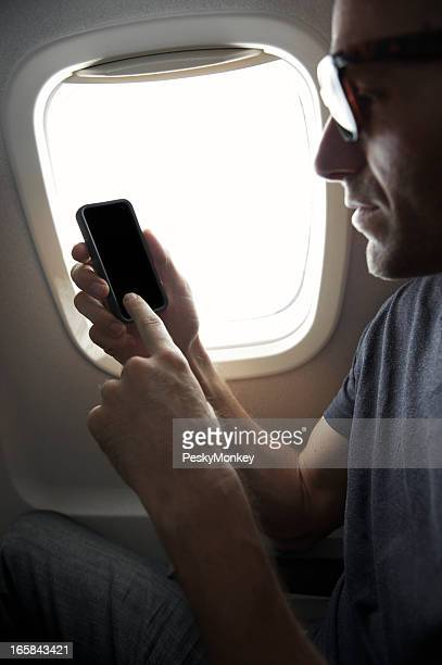 Airplane Passenger Using Smart Phone Sitting in Window Seat