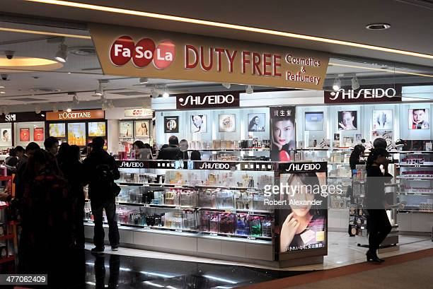 Airplane passengers between flights browse at a FaSoLa duty free cosmetics and perfume shop at Narita International Airport near Tokyo