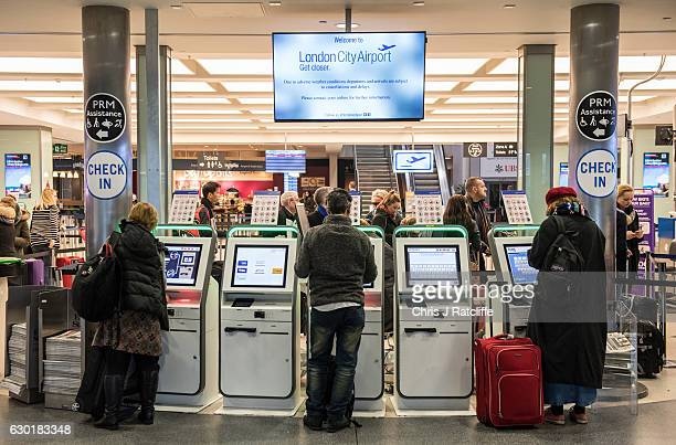 Airplane passengers check in at London City Airport as a sign above warns of delays and cancellations due to fog on December 18 2016 in London...