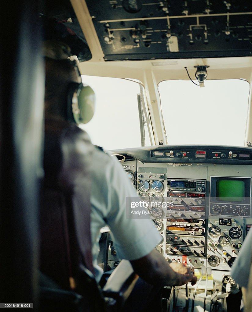 Airplane pilot seated at controls, rear view : Stock Photo