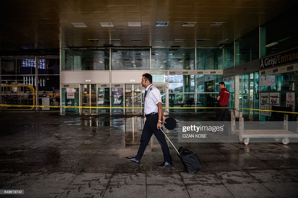 A airplane pilot (C) walks past a cordoned off area as an employee of a private security company looks on, outside Ataturk airport's international arrivals terminal on June 29, 2016, a day after a suicide bombing and gun attack targeted Istanbul's airport, killing at least 36 people. A triple suicide bombing and gun attack that occurred on June 28, 2016 at Istanbul's Ataturk airport has killed at least 36 people, including foreigners, with Turkey's prime minister saying early signs pointed to an assault by the Islamic State group. / AFP / OZAN