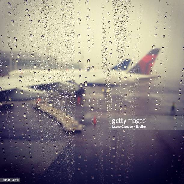 Airplane seen through wet airport glass