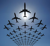 Rows of many planes flying in the sky. Clear blue sky, shot against the sun. Check out some other aviation files: [url=http://www.istockphoto.com/file_search.php?action=file&lightboxID=8986312] [img]h