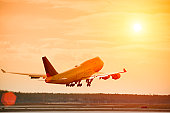 Airplane taking off at sunset, lens flare, copy space