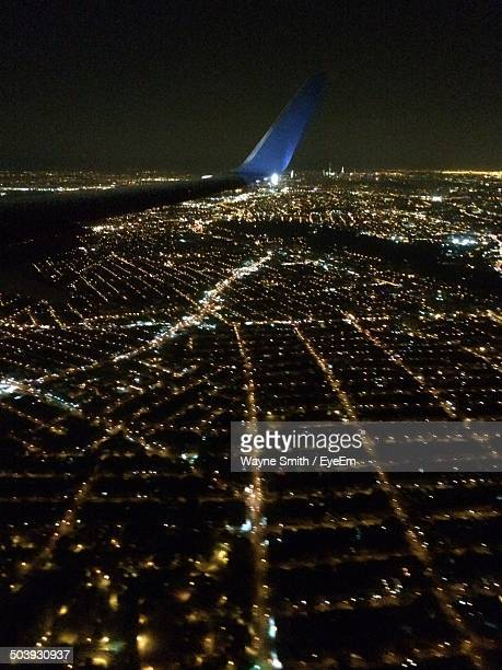 Airplane wing over illuminated city at night