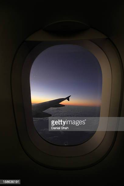 Airplane wings and window sunrise above clouds
