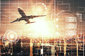 Airplane on city background with digital business chart interface and sunlight. Technology concept. Double exposure