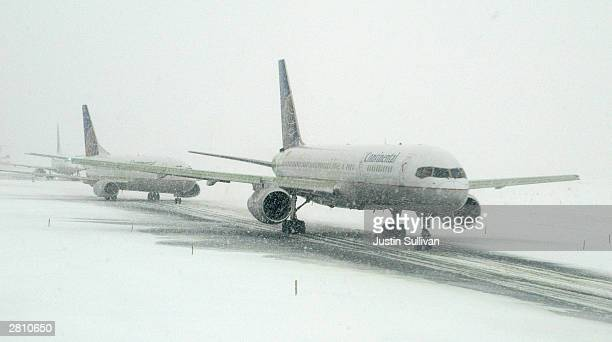 Airplanes taxi on a snow covered runway at Newark Liberty International Airport December 14 2003 in Newark New Jersey Approximately three to six...