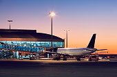 Preparation of the airplane before flight. Airport at the colorful sunset.