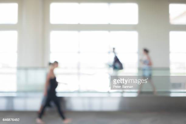 Airport, blurred focus as 3 people walk past with wheeled luggage