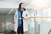 Airport business woman with smart phone at gate waiting in terminal. Air travel concept with young casual businesswoman. Beautiful young tourist girl with luggage in international airport.