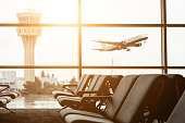 Empty chairs in the departure hall at airport , with the control tower and an airplane taking off at sunset. Travel and transportation concepts.