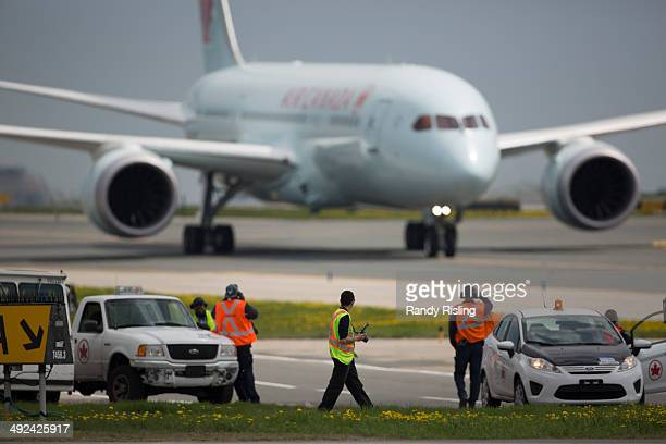 Airport employees take photos of Air Canada's new 787 Dreamliner as it comes in for a water cannon salute at Toronto Pearson International Airport...