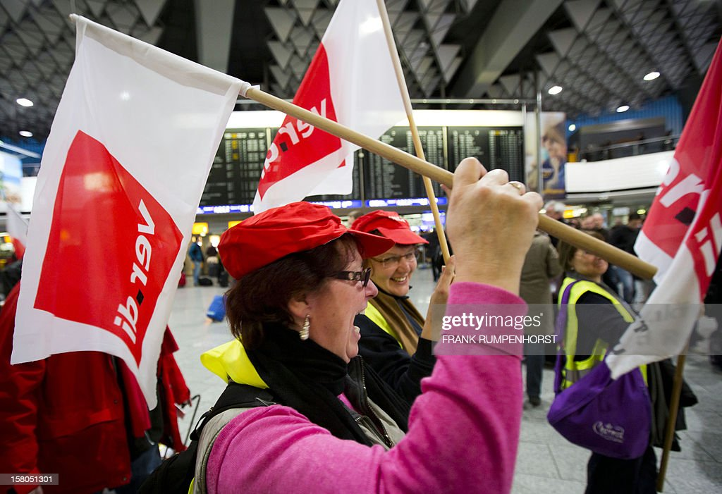 Airport employees wave flags with the logo of German services union Verdi as they stage a strike on December 10, 2012 at the airport in Frankfurt am Main, western Germany. Airport security personnel in Germany staged warning strikes in a dispute over pay, bringing disruption to several German airports. AFP PHOTO / FRANK RUMPENHORST GERMANY OUT