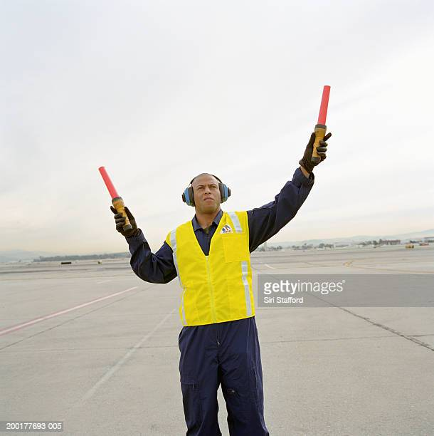 Airport ground crew directing aircraft