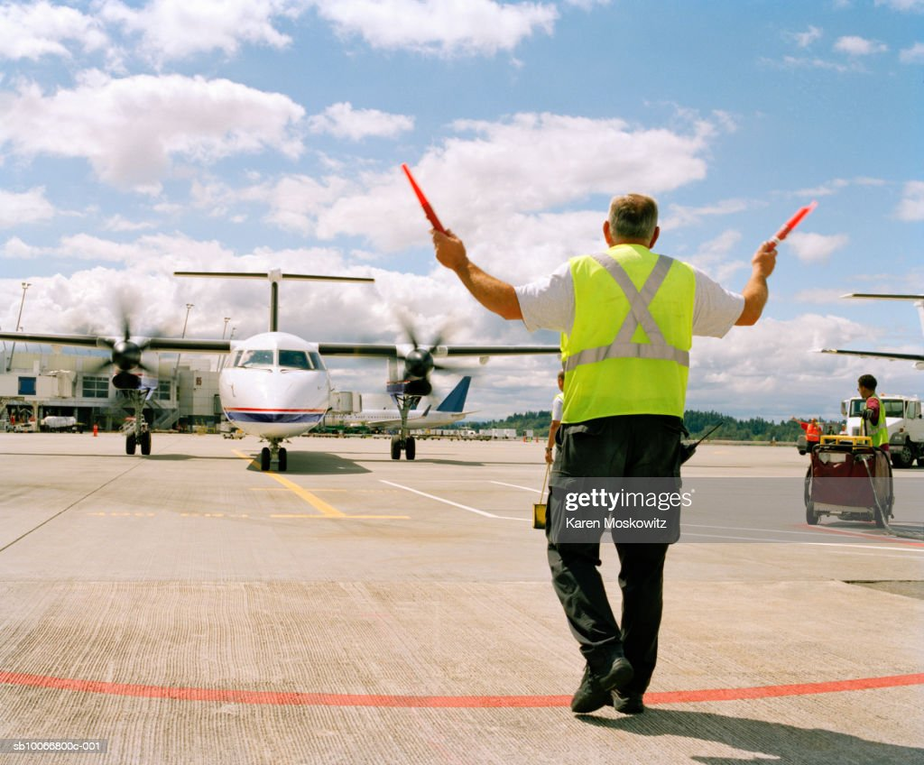 Airport ground crew directing aircraft, rear view