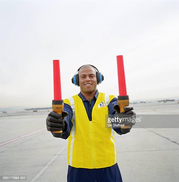 Airport ground crew holding signaling sticks