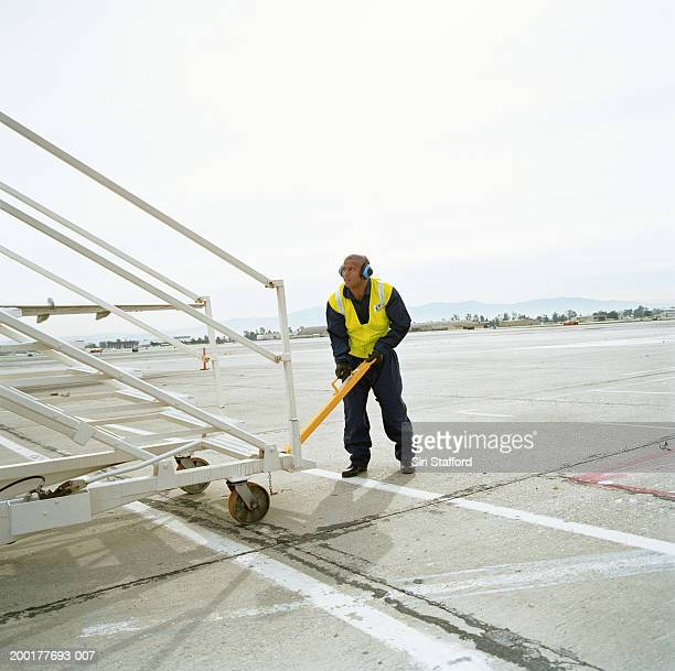 Airport ground crew preparing aircraft stairs