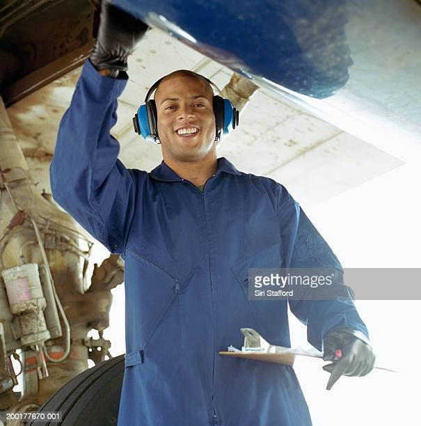 Airport ground technician inspecting aircraft, holding clipboard