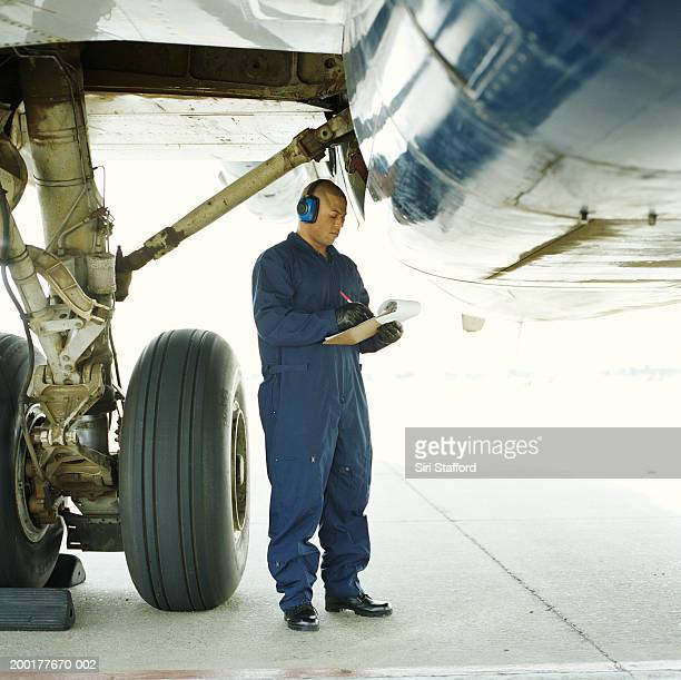 Airport ground technician inspecting aircraft, wearing headphones