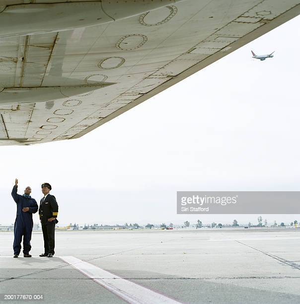 Airport ground technician inspecting plane with pilot