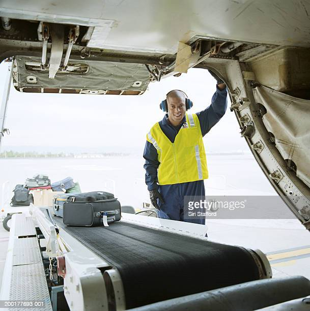 Airport ground technician loading luggages into cargo hold of aircraft