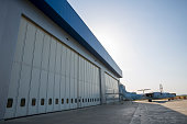 Airport hangar from the outside with big tall doors. Bright blue sky.