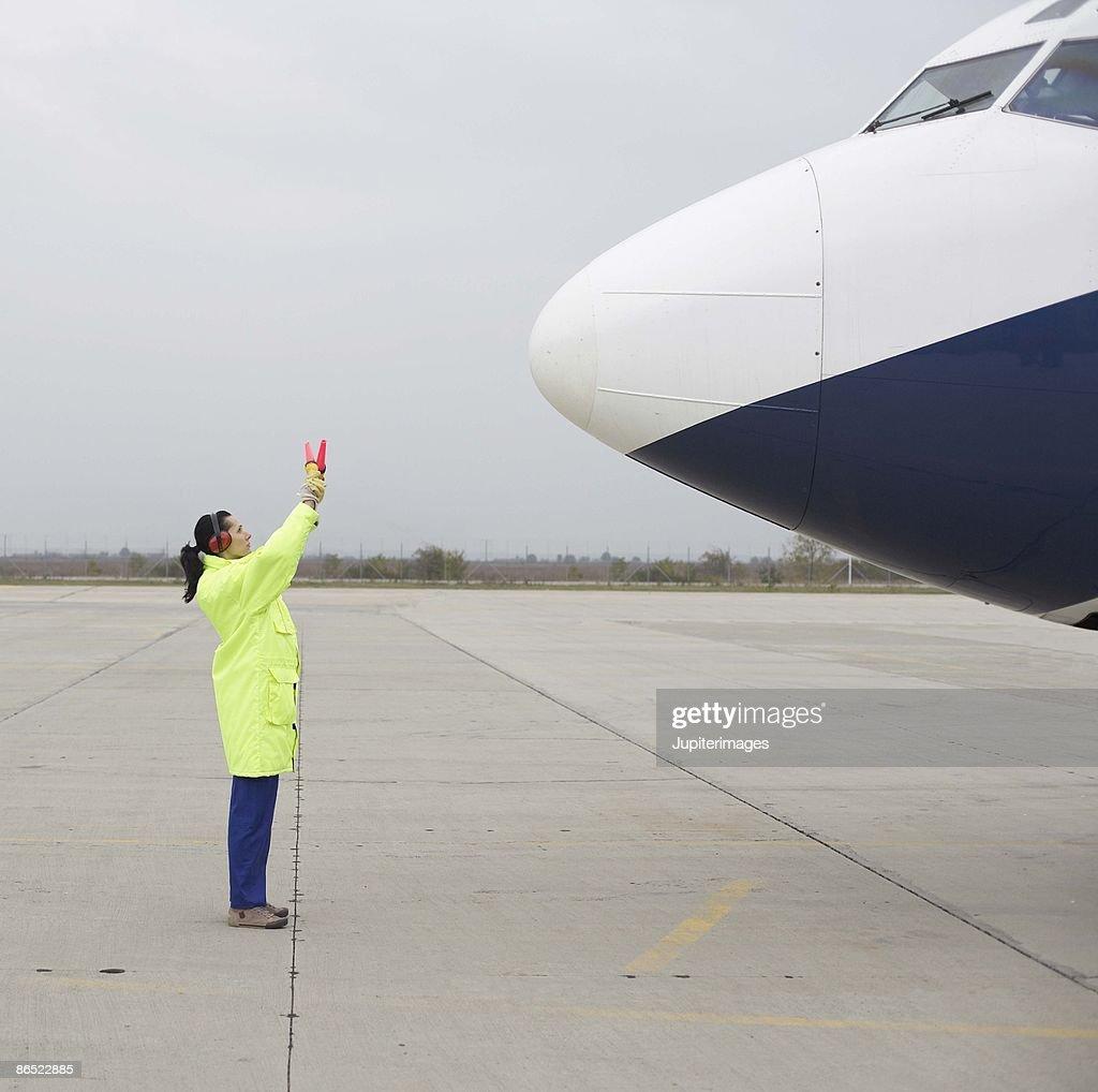 Airport hangar worker directing airplane on tarmac