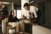 Business lounge waitress serving coffee to female passenger at waiting area. Business woman relaxing and waiting for flight at airport departure lounge.