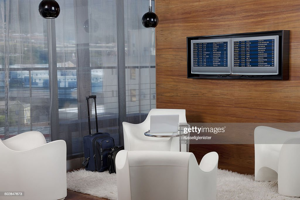 Airport lounge with travel bag, laptop and departure boards : Stock Photo