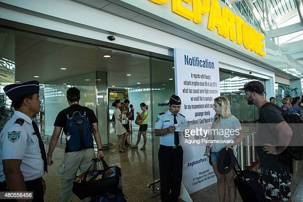 Airport officer reads the flight schedule of the tourist at Ngurah Rai international airport departure on July 13 2015 in Denpasar Bali Indonesia...