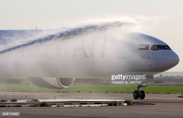 Airport officials spray water on the first Boeing 777300ER ordered by Kuwait Airways after it landed at Kuwait International Airport on December 9 in...