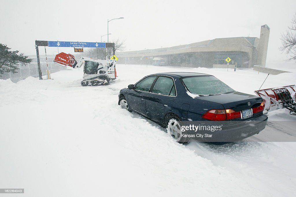 Airport plows assist a stuck drive outside one of the Kansas City International Airport terminals Thursday morning, February 21, 2013.
