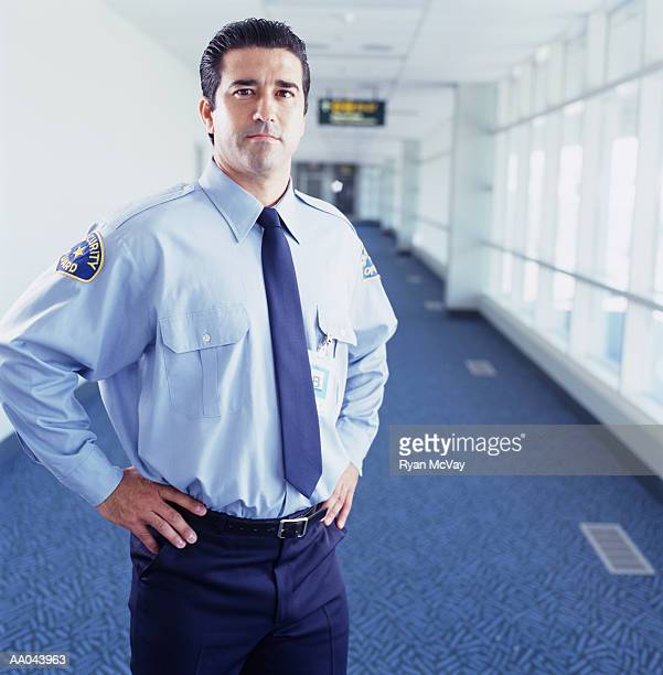 Airport security guard standing with hands on hips, portrait