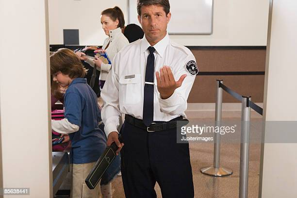 Airport security officer directing passengers through security checkpoint
