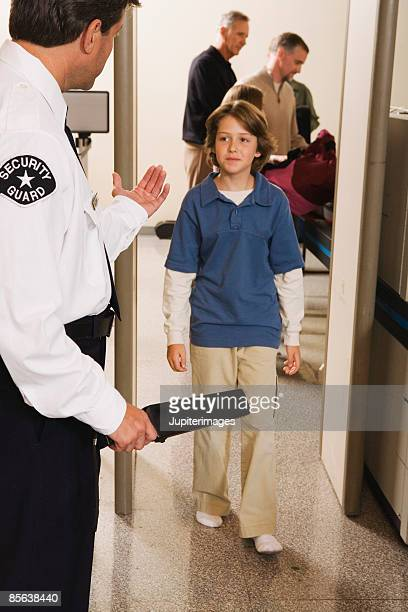 Airport security officer directing pre-teen boy through security checkpoint