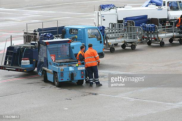 Airport service in orange shirts standing by blue vehicles